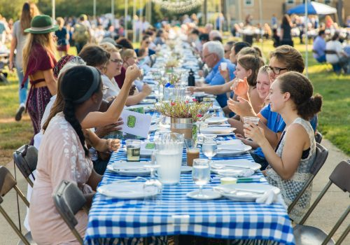 People chatting and dining at UNC Asheville's Farm-to-Table Dinner.